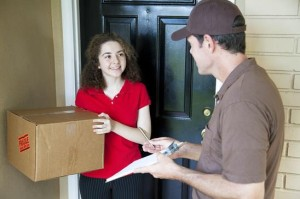 Delivery man brings a package to a customer's door and waits for a signature.