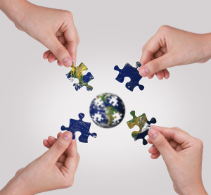 photodune-1028970-business-concept-with-a-hand-building-puzzle-globe-s